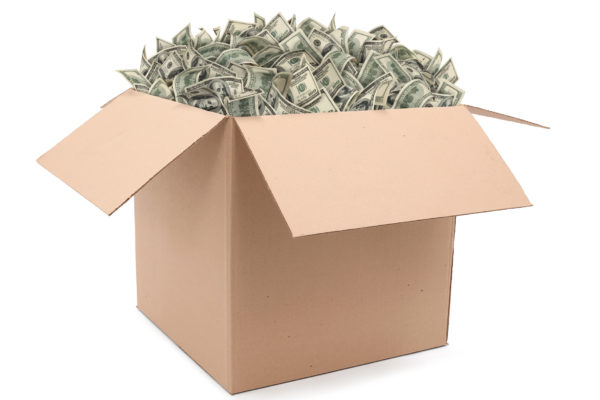 Cardboard box overflowing with money (one hundred-dollar bills). Isolated on white background.